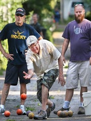 Jim Kelly tosses his orange bocce ball down a brick-lined alley between Broadway Street and Park Avenue.