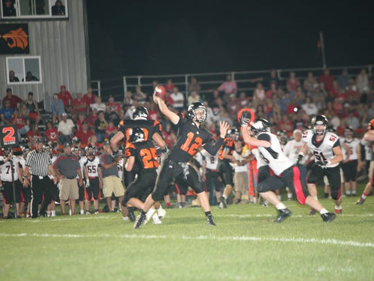 Grinnell's quarterback Cade McKnight prepares to throw a pass while a Raider defender closes in during action Friday night at Grinnell. After being down 13-0 early, the Tigers came roaring back late in the fourth quarter to capture the 24-23 win on a missed Radier field goal.