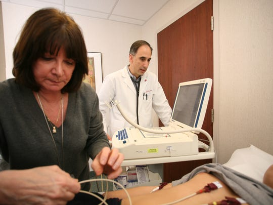 Dr. Steven Georgeson, M.D., a staff cardiologist at Robert Wood Johnson University Hospital (RWJUH) at Somerset conducts a cardiac screening test on a high school student athlete.