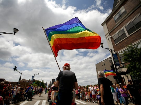 Paul Johnson of Des Moines waves a flag while walking down Locust Street in the Capital City Pride parade, part of Pridefest 2013.