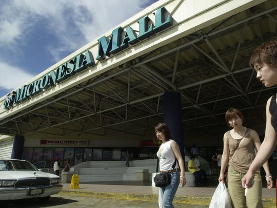Tourists cross the street in front of the Micronesia Mall.