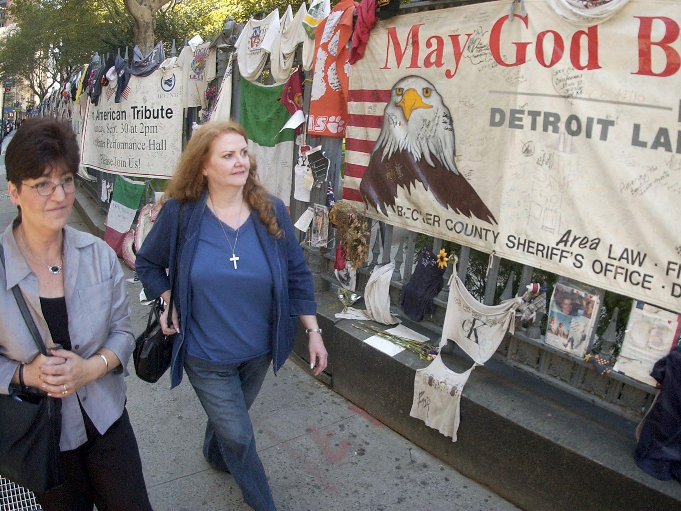 Margaret Gramly walks with her therapist past memorials