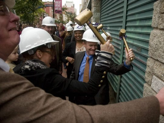 Then-county executive Chris Coons, World Cafe Live founder Hal Real and others tap the Queen during the groundbreaking of the Queen Theater on Market Street in Wilmington in October 2009.