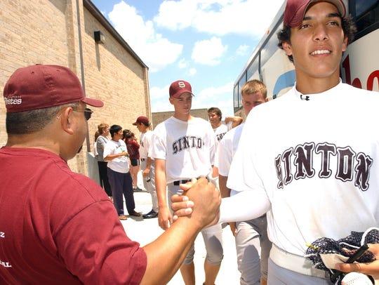 Sinton's Jason Adams and his teammates receive handshakes
