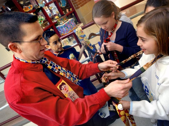 In this 2004 file photo, Joel Gugino, left, gives a lesson in tying a tie to a student at Sinking Springs Elementary School.