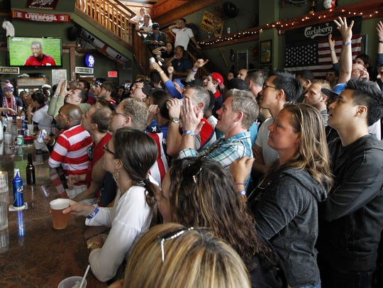 Fans cheer at Nomad World Pub during the 2014 World