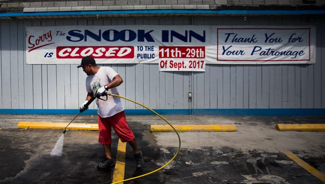 Roberto Valesquez pressure washes the parking lot at the Snook Inn on Marco Island on Tuesday, September 12, 2017, two days after Hurricane Irma.