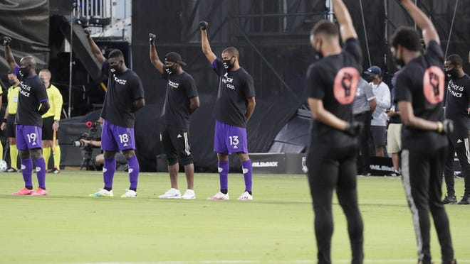 Orlando City players raise their fists in the air in solidarity with other MLS teams before the start of an MLS soccer match on Wednesday, July 8, 2020, in Kissimmee, Fla.