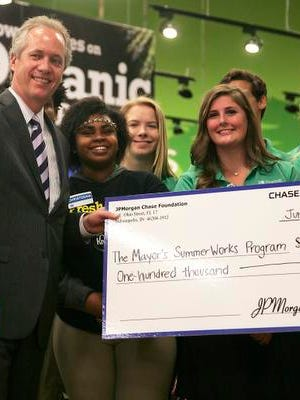 Mayor Greg Fischer and participants in the Louisville SummerWorks program hold up a check donated by the JPMorgan Chase foundation during a press conference at the Kroger on W. Broadway.