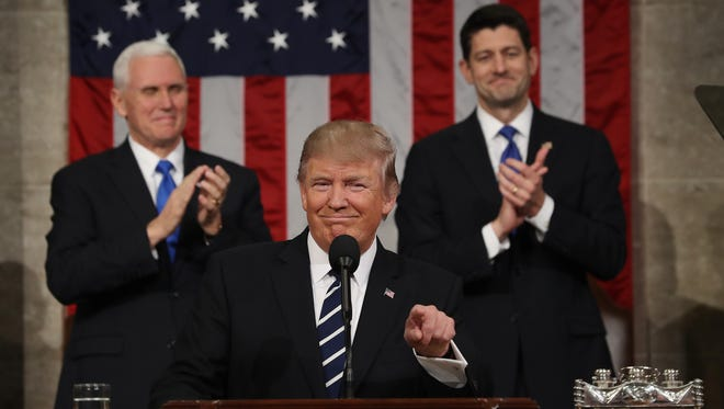 U.S. Vice President Mike Pence and Speaker of the House Paul Ryan applaud as U.S. President Donald J. Trump arrives to deliver his first address to a joint session of the U.S. Congress on Tuesday in the House chamber of the U.S. Capitol in Washington, DC.