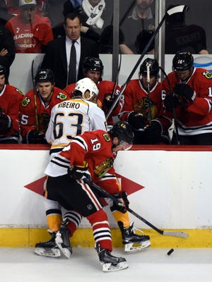 Chicago Blackhawks center Jonathan Toews (19) and Nashville Predators center Mike Ribeiro (63) go for the puck during the third period in game three of the first round of the 2015 Stanley Cup Playoffs at the United Center.
