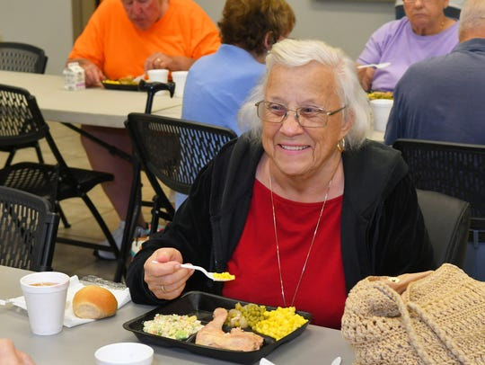 Rosemary Farrow, 76, shown eating at Seniors at Lunch program at the Cuyler Park Community Center in Mims, says the Reaching Out campaign helps assure lonely people don't feel left out during the holidays.