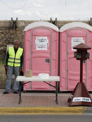 Municipal workers manage portable toilets near a line to enter the U.S. at a border crossing in Ciudad Juarez, Mexico, on April 5. The city has brought in the toilets, and an engine oil company hired models to hand out burritos and bottled water to idled drivers.