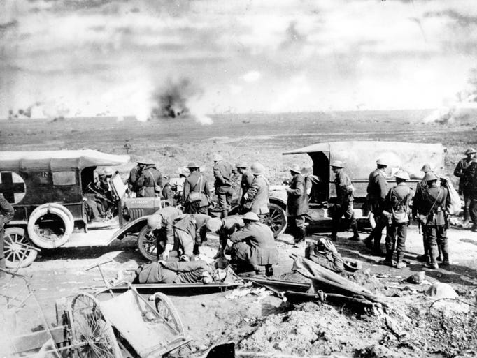 Wounded soldiers are given aid and loaded into a Red Cross ambulance on the British front lines in France during World War I. Smoke from battle can be seen in the background in this undated photograph. (AP Photo)
