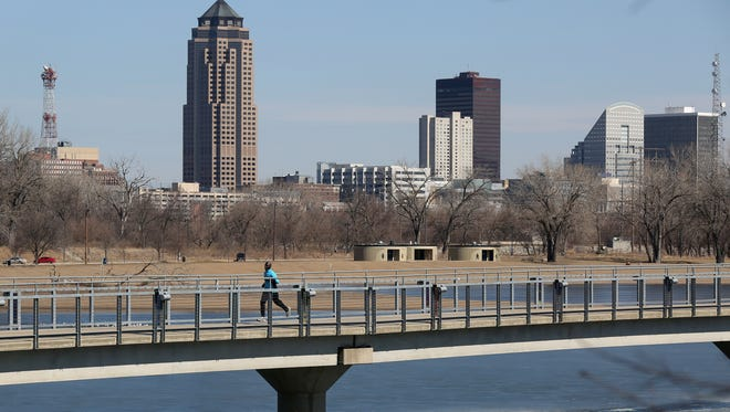 A jogger crosses the bridge at Gray's Lake Park with the Des Moines skyline in the background on Thursday, March 20, 2014, as temperatures at noon reached the low 50s.