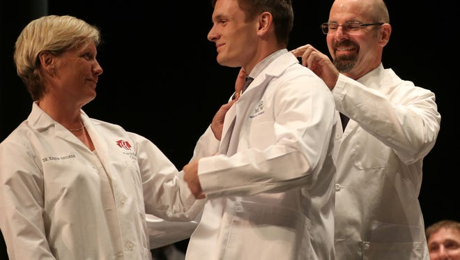 Alexander Schulman is coated during the Medical College of Wisconsin Central Wisconsin White Coat Ceremony at UW Marathon County, in Wausau, Wisconsin, July 7, 2016.