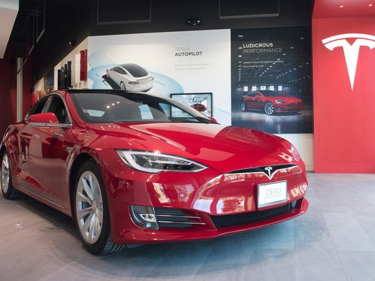 A new Tesla Model S 90D in red greets customers at