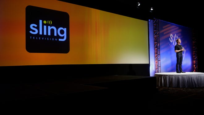 Roger Lynch, far right, CEO of Sling TV, demonstrates on Sling TV, a live television streaming service, at the Dish Network's news conference at the International CES, Monday, Jan. 5, 2015, in Las Vegas.
