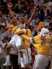 UCLA's Tyus Edney jumps into the arms of a teammate as they celebrate their 75-74 win over Missouri in the NCAA West Regionals Sunday, March 19, 1995, in Boise, Idaho. (AP Photo/Indianapolis News, Paul Sancya) ORG XMIT: BDS115