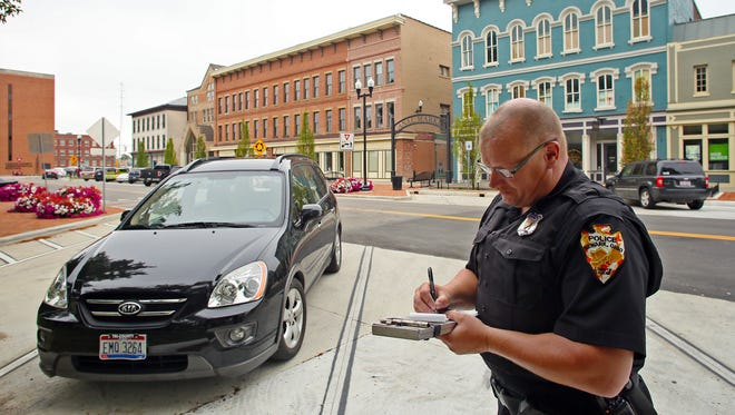 Newark Police Officer Ray Lewis issues warnings for vehicles parked longer than two hours around Courthouse Square Friday morning. Soon, the maximum amount of time a vehicle can be parked on the square will change from three to two hours a day.