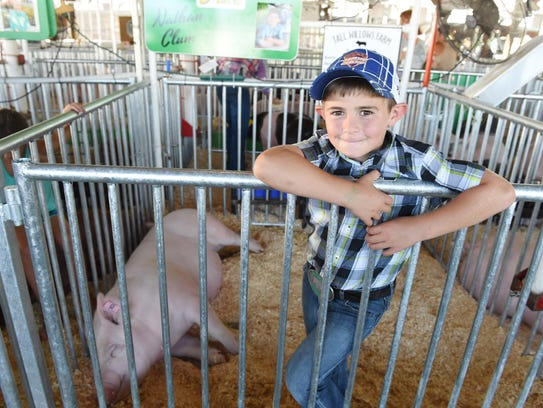 Nathan Clum, 6 of Red Hook stands beside his pig, Suzy,
