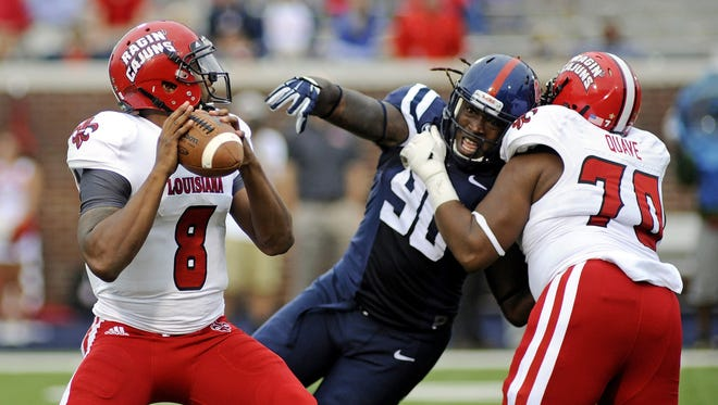 Louisiana-Lafayette quarterback Terrance Broadway (8) prepares to throw as offensive linesman Mykhael Quave (70) blocks Mississippi defensive end Fadol Brown (90) during the second half of an NCAA college football game in Oxford, Miss., Saturday, Sept. 13, 2014. No. 14 Mississippi won 56-15. (AP Photo/The Daily Mississippian, Thomas Graning)