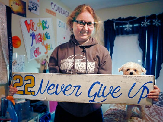 FILE - In this Dec. 8, 2014, file photo, Lauren Hill holds a sign made for her, which she keeps in her room, along with many other messages and gifts of support. Hill, a freshman at a Ohio university who fought an inoperable brain tumor to play college basketball, died Friday, April 10, 2015, in Cincinnati . She was 19. (AP Photo/The Enquirer, Carrie Cochran, File) NO SALES
