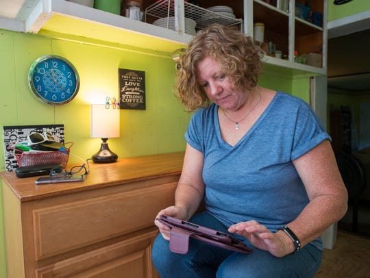 Dawn Stone checks her insurance policy on her tablet