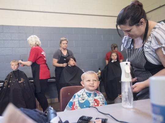 Cohen Taylor, 4, from Huntington Township, gets his hair cut along with several other school age children as part of the Project School Tools program.