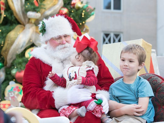 Blaze Jordan, 6, right, contemplates what to say to Santa as his 10-month-old sister, Bella, checks out the man in red before the Elf Parade in downtown Pensacola on Friday, Nov. 24, 2017.