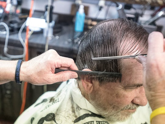 Hank Malone not only uses scissors to cut hair, but