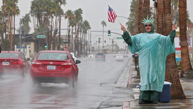 In a steady drizzle Jason Eien promotes Liberty Tax Service in Palm Springs during the year's first rainfall, January 5, 2015.