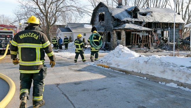 Members of the Wauzeka fire department work the aftermath of a house fire that took the lives of two people, Tuesday, Jan. 19, 2015. Two girls have died in a house fire in Crawford County.Sheriff's officials say the victims are ages 12 and 15. Firefighters were called to a house in the Village of Wauzeka about 11:30 p.m. Monday. (Dave Kettering/Telegraph Herald via AP)