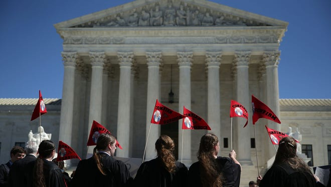 Members of the group Public Advocate of the U.S. hold up signs to support the Gorsuch nomination during a news conference in front of the Supreme Court on March 29, 2017.