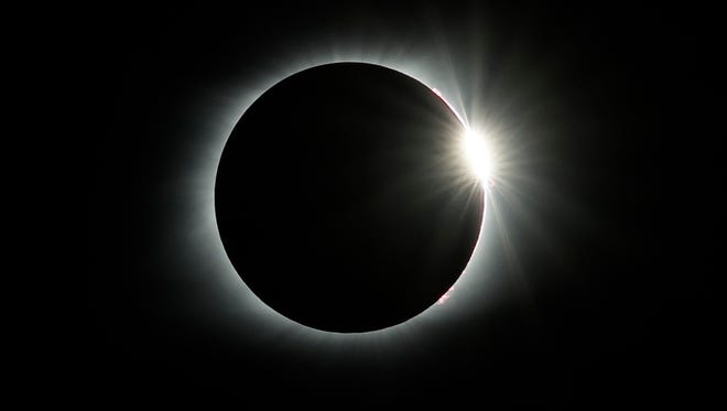 The diamond ring effect appears as the solar eclipse totality ends Monday, Aug. 21, 2017, over the Orchard Dale historical farm near Hopkinsville, Ky.