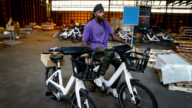 Cherance King tests assembled bikes, as Explore Bike Share staff put together 600 for-rent bicycles and 60 docking stations that will be placed around the city before their May 23 launch.