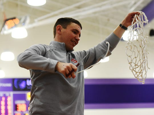 Sheridan coach J.D. Walters holds up the net after