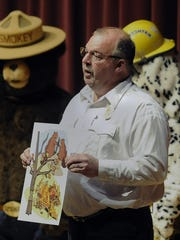 """Pittsville Fire Chief Jerry Minor holds an oversized fire safety flashcard to teach youngsters about """"good"""" and """"bad"""" wildfires while speaking to an assembly of students from Pittsville in 2014. Minor is disappointed his efforts to get a novelty lighter law passed by the State Legislature failed at the last minute this year."""