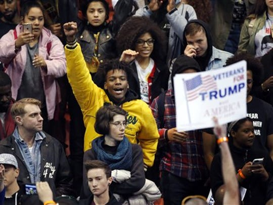 A protester raises his fist to supporters of Republican presidential candidate Donald Trump before a rally on the campus of the University of Illinois-Chicago, Friday, March 11, 2016, in Chicago.