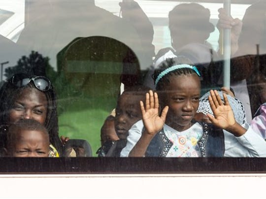 A family look out of the window of a bus after being evacuated from Brussels airport, after explosions rocked the facility in Brussels, Belgium, Tuesday March 22, 2016. Authorities locked down the Belgian capital on Tuesday after explosions rocked the Brussels airport and subway system, killing at least 13 people and injuring many more. Belgium raised its terror alert to its highest level, diverting arriving planes and trains and ordering people to stay where they were. Airports across Europe tightened security. (AP Photo/Geert Vanden Wijngaert)