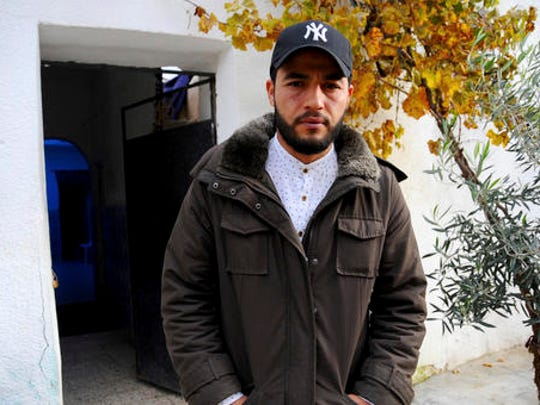 """The brother of fugitive Tunisian extremist suspected in Berlin's deadly Christmas market attack, Abdelkader Amri, poses for a photo in front of the family house where Anis Amri used to live, in Oueslatia, central Tunisia, Thursday, Dec. 22, 2016. Brother Abdelkader Amri told The Associated Press, """"I ask him to turn himself into the police. If it is proved that he is involved, we dissociate ourselves from it."""""""