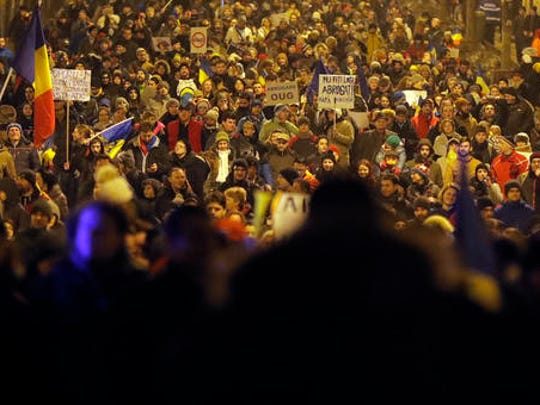 Demonstrators march in front of the government building during a protest in Bucharest, Romania, Saturday, Feb. 4, 2017. On Saturday, thousands of Romanians took to the streets for a fifth consecutive day to protest the decree, that waters down the country's anti-corruption fight. The latest outpouring of public anger resolved in the largest demonstrations since communism ended.