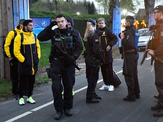 FILE - In this April 11, 2017 file photo Dortmund's Marcel Schmelzer, third from right, talks to police officers outside the team bus after it was damaged in an explosion before the Champions League quarterfinal soccer match between Borussia Dortmund and AS Monaco in Dortmund, western Germany.