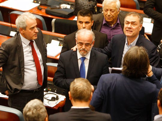 Talat Xhaferi, center, a senior official of the ethnic Albanian Democratic Union for Integrations, stands after being elected as a new speaker in the parliament building in Skopje, Macedonia, Thursday, April 27, 2017. Scores of protesters in Macedonia have broken through a police cordon and entered parliament to protest the election of a new speaker despite a months-long deadlock in talks to form a new government.