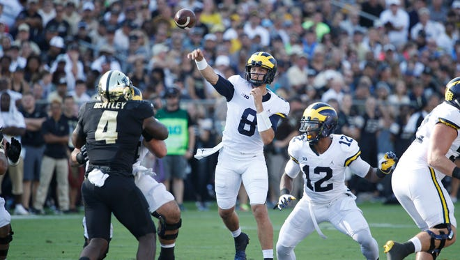 Michigan quarterback John O'Korn throws a pass in the second quarter against Purdue, as Chris Evans (12) looks for a block at Ross-Ade Stadium in West Lafayette, Ind. on Sept. 23, 2017. O'Korn finished with 270 yards and a touchdown.