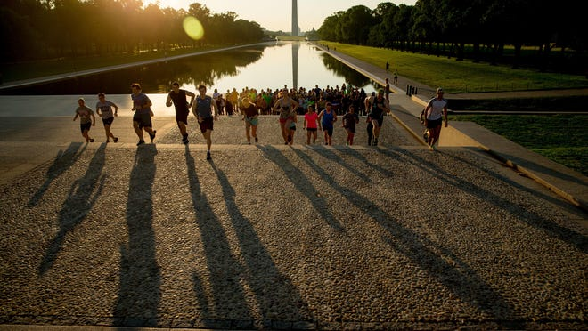 """Members of the running group November Project run up and down the stairs near the Lincoln Memorial, in Washington. Fitness buffs around the country are bringing the """"take the stairs"""" advice to a whole new level as noteworthy landmarks have become unlikely, yet popular, new workout sites."""