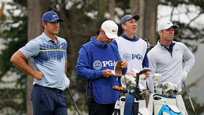 Brooks Koepka (left) stands next to his caddie Ricky Elliott along with Paul Casey (right) and his caddie John McLaren in the tee box of the 4th hole during the final round of the PGA Championship at TPC Harding Park.