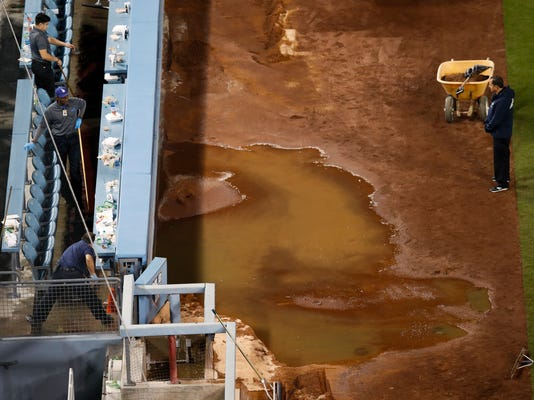 Workers sweep the water away after a water pipe broke near third base at Dodger Stadium, after an exhibition baseball game between the Los Angeles Dodgers and the Los Angeles Angels, Tuesday, March 27, 2018, in Los Angeles. (AP Photo/Jae C. Hong)
