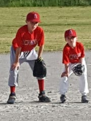 Mathew Thibodeau (left) gives tips on proper stance in the infield to Little Angel Brady Milligan.
