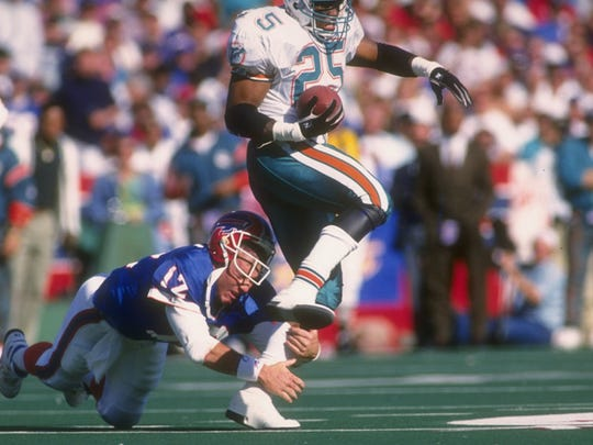 Jim Kelly tries to tackle defensive back Louis Oliver of the Miami Dolphins during a game at Rich Stadium on Oct 4, 1992.